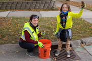 Adult and child cleaning a stormdrain.