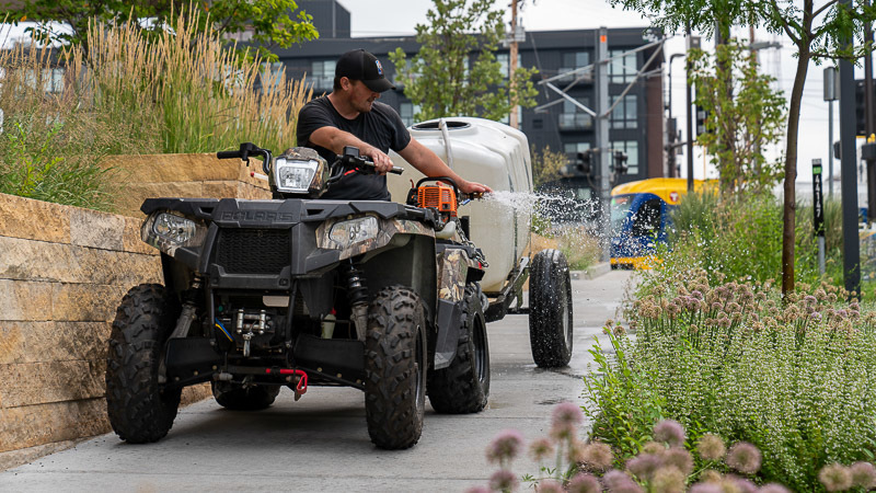 A worker watering plants from an ATV.