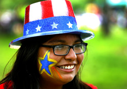 Person smiling, wearing a hat of stars and stripes with a star painted on their cheek