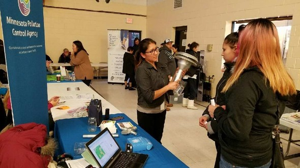Little Earth School Choice and Resource Fair learning about air monitoring
