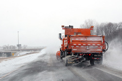 Snow plow spreading salt