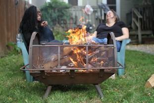 People sitting around a backyard fire