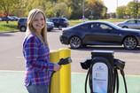 Woman using Level 2 EV charging station