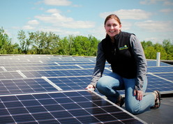 GreenCorps member in front of solar roof panels