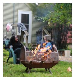 Two women enjoy a backyard fire and a beverage