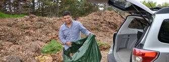 Man emptying bag of leaves at yard waste site