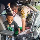 An officer shows a boy the inside of a squad car.