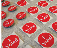Three photos: Emergency Communications Center, I voted stickers, girl reading book
