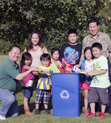 Hmong family standing by a recycling container