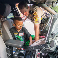 Deputy showing child the interior of the cruiser