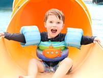 boy sliding down water slide