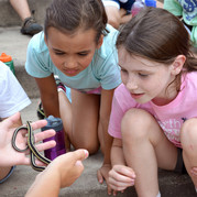 Two girls looking at snake while attending day camp