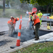 public works employees repairing section of road