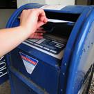 Person putting ballot into mailbox