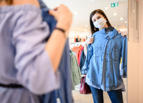 Woman wearing a mask while shopping at a thrift store.