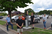 People stand near an electric vehicle charging station.