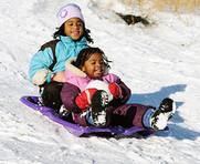 Residents sledding down hill
