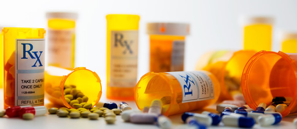 Stock photo: Prescription pill bottles lined up against a white background. Some bottles are open and tipped over with pills spilling out.