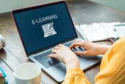 """Stock photo: hands on a laptop keyboard. The laptop displays the word """"E-learning"""" on its screen."""