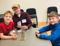 student with senior playing cribbage
