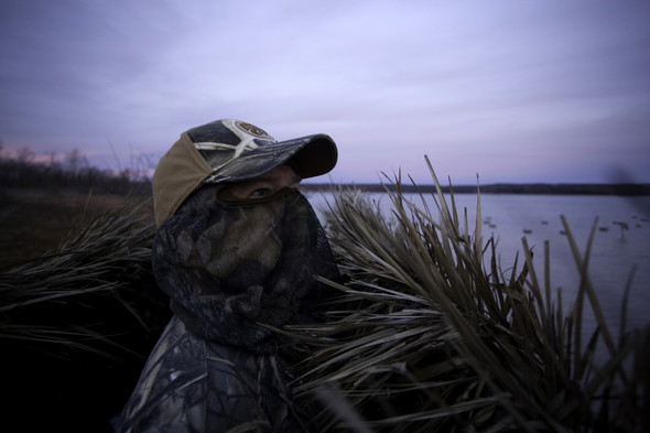 A waterfowl hunter in complete camo looks out over a marsh before sunrise.
