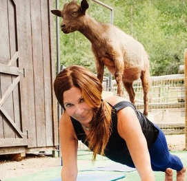 Woman doing yoga with a goat on her back