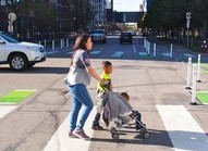 Woman crossing marked crosswalk with children