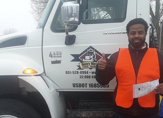 man with certificate in front of truck