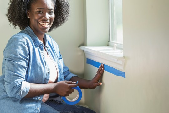 woman taping window sill before painting