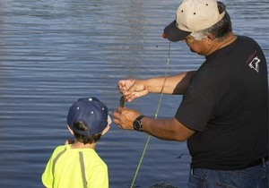 Volunteer youth fishing instructor with a boy.