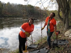 women planting trees by stream