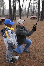 DEC staff teaching a child to cast