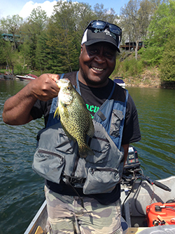 A man holding up a black crappie