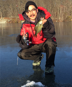 Angler with a crappie caught through the ice