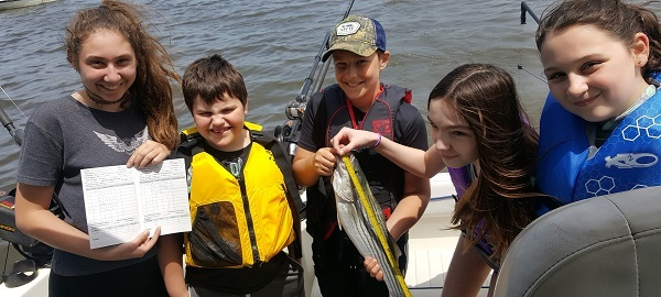 Four children on a boat with a using a measuring tape to measure a striped bass they caught.