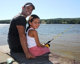 A young man helps his daughter hold a fishing pole on a stone wall by the Hudson River.