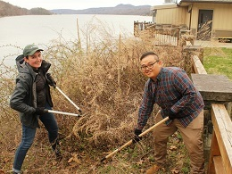A young woman is cutting brush with loppers and a young man is loosening soil with a hoe by the Hudson River