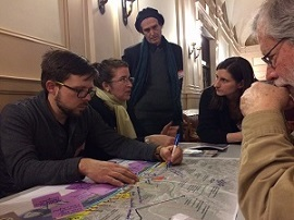A group of five adults gather around a map of Kingston in a room. One woman is holding a highlighter.
