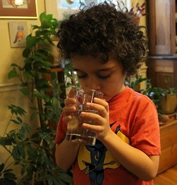 A young boy drinks a glass of water.