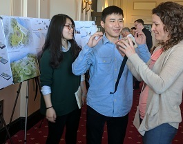 Two graduate students discuss their design for a resilient waterfront displayed on a poster to a woman.