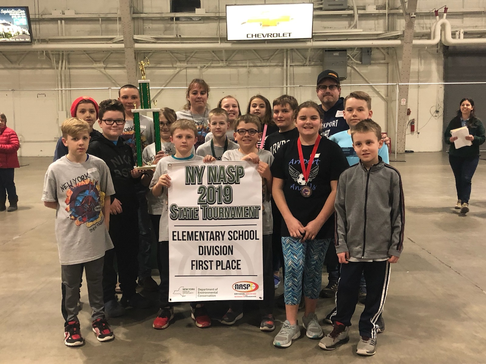 Elementary school archers pose with the tournament sign