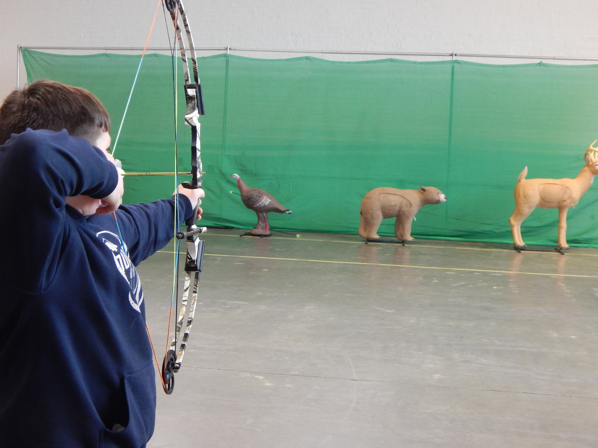 An archer takes aim at a 3D target in a school gym.