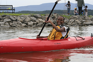 Young child learning to kayak on a small pond at an outdoors day event