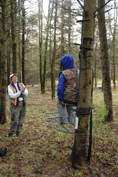 A BOW instructor talks about tree stand safety with a student in the stand.