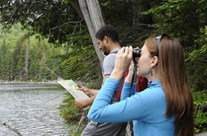 people bird watching with map and binoculars