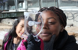 Two students look at a plastic instrument called a hydrometer to check the salinity of the water in New York Harbor.