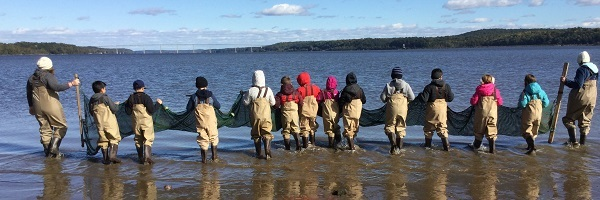 12 young students and 2 teachers in waders hold a long net and stand on the shore of the Hudson at Kingston Point beach.