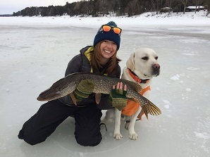 woman on ice holding fish with dog