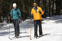 A couple cross country skiing on groomed snow trails at Camp Santanoni