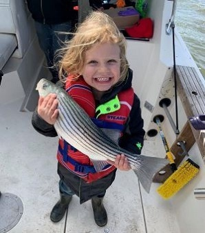 Little girl on a boat holding a striped bass